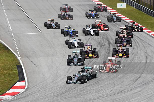 Lewis Hamilton of Great Britain and Mercedes GP leads from Sebastian Vettel of Germany and Ferrari in to the first corner during the Malaysia Formula...