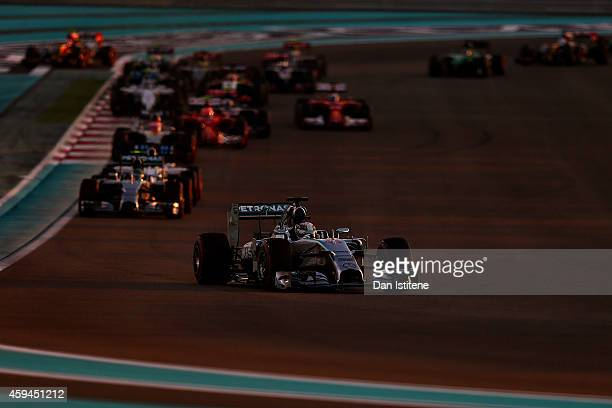 Lewis Hamilton of Great Britain and Mercedes GP leads Nico Rosberg of Germany and Mercedes GP and the rest if the field into turn two during the Abu...