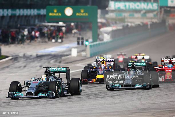 Lewis Hamilton of Great Britain and Mercedes GP leads Nico Rosberg of Germany and Mercedes GP at the first corner during the Malaysia Formula One...