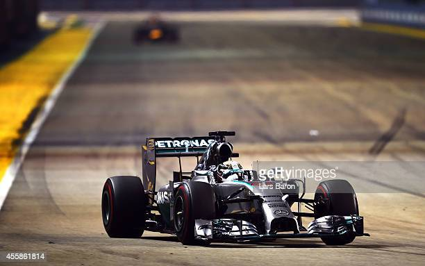 Lewis Hamilton of Great Britain and Mercedes GP leads Sebastian Vettel of Germany and Infiniti Red Bull Racing during the Singapore Formula One Grand...