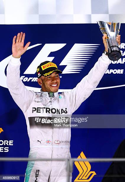 Lewis Hamilton of Great Britain and Mercedes GP lifts the trophy as he celebrates on the podium after winning the Singapore Formula One Grand Prix at...