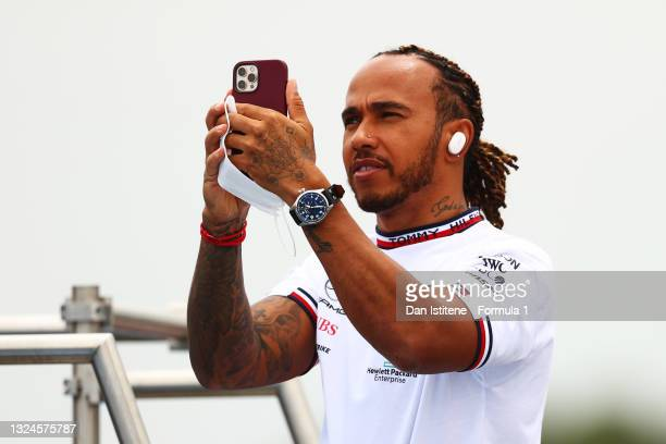 Lewis Hamilton of Great Britain and Mercedes GP looks at his phone as he rides a truck on the track to show his appreciation for the fans during the...