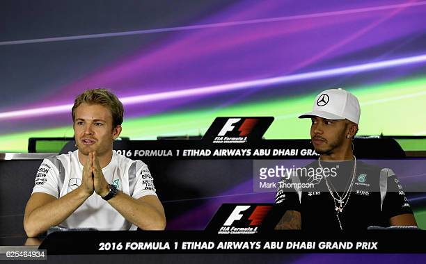 Lewis Hamilton of Great Britain and Mercedes GP looks on while Nico Rosberg of Germany and Mercedes GP talks as the World Drivers Championship...
