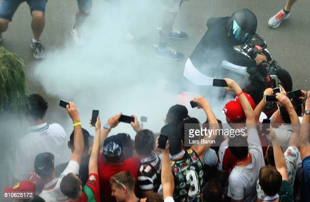 Lewis Hamilton of Great Britain and Mercedes GP performs burn outs on a motorcycle for fans before final practice for the Formula One Grand Prix of...