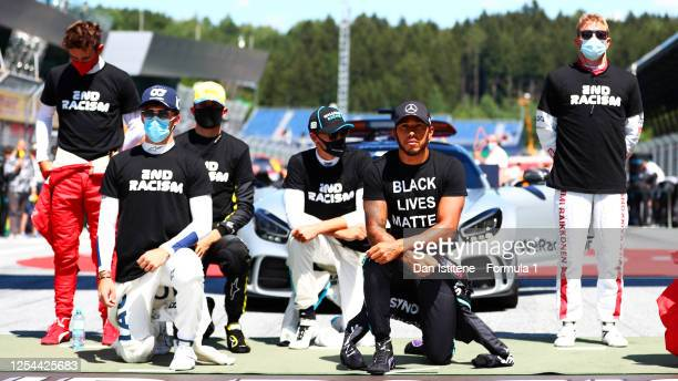 Lewis Hamilton of Great Britain and Mercedes GP Pierre Gasly of France and Scuderia AlphaTauri and some of the F1 drivers take a knee on the grid in...