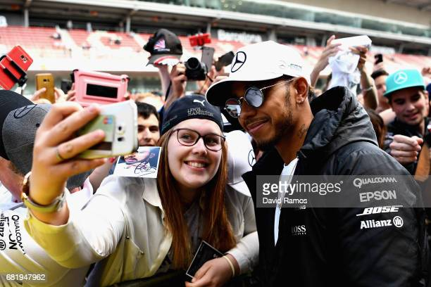 Lewis Hamilton of Great Britain and Mercedes GP poses for a photo with a fan during previews for the Spanish Formula One Grand Prix at Circuit de...