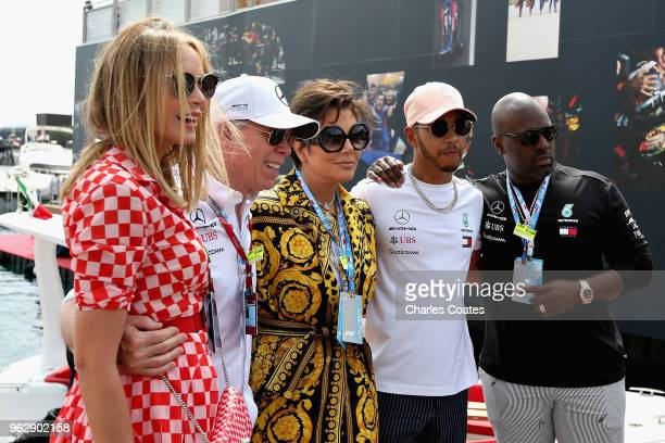 Lewis Hamilton of Great Britain and Mercedes GP poses for a photo with Dee Hilfiger Tommy Hilfiger Kris Jenner and Corey Gamble in the Paddock before...