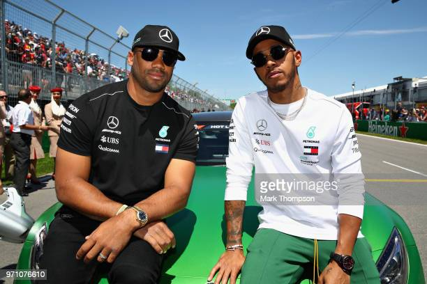 Lewis Hamilton of Great Britain and Mercedes GP poses for a photo with Seattle Seahawks Quarterback Russell Wilson before the Canadian Formula One...