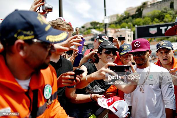 Lewis Hamilton of Great Britain and Mercedes GP poses for a selfie with a fan during previews to the Monaco Formula One Grand Prix at Circuit de...