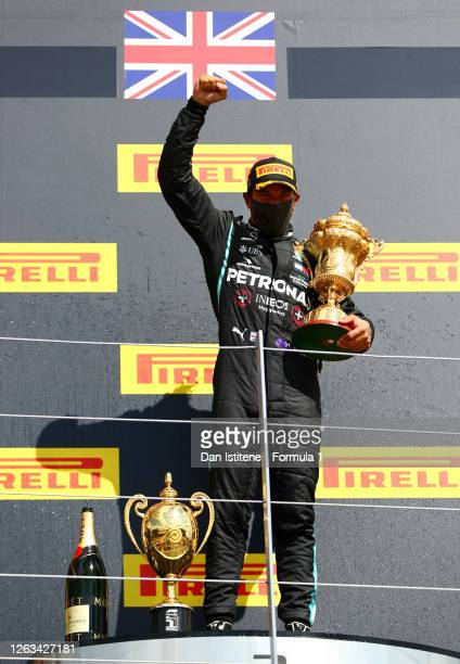 Lewis Hamilton of Great Britain and Mercedes GP raises his fist as he celebrates on the podium after winning the Formula One British Grand Prix at...