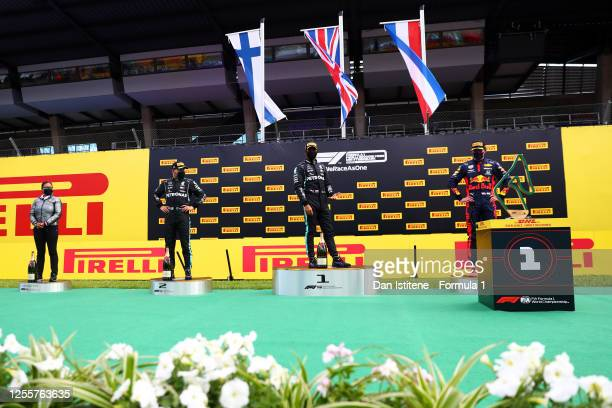 Lewis Hamilton of Great Britain and Mercedes GP reacts next to Max Verstappen of Netherlands and Red Bull Racing and Valtteri Bottas of Finland and...