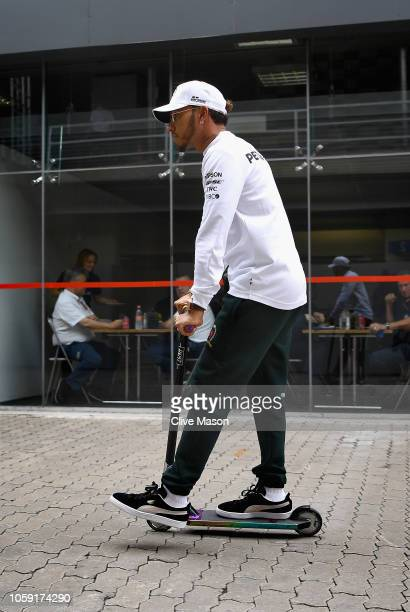 Lewis Hamilton of Great Britain and Mercedes GP rides a scooter in the Paddock during previews ahead of the Formula One Grand Prix of Brazil at...