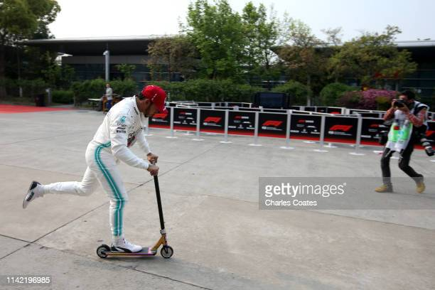 Lewis Hamilton of Great Britain and Mercedes GP rides a scooter in the Paddock during practice for the F1 Grand Prix of China at Shanghai...