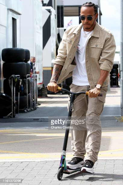 Lewis Hamilton of Great Britain and Mercedes GP rides a scooter in the Paddock during previews ahead of the F1 Grand Prix of Great Britain at...