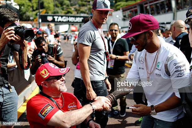 Lewis Hamilton of Great Britain and Mercedes GP shakes hands with a fan during previews to the Monaco Formula One Grand Prix at Circuit de Monaco on...