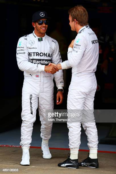 Lewis Hamilton of Great Britain and Mercedes GP shakes hands with teammate Nico Rosberg of Germany and Mercedes GP after qualifying in pole position...