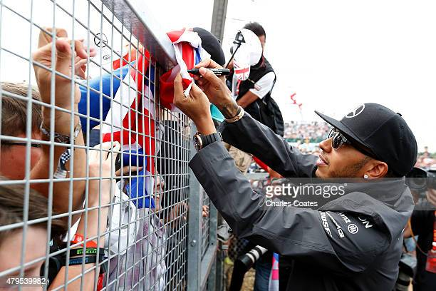 Lewis Hamilton of Great Britain and Mercedes GP signs autographs for fans before the Formula One Grand Prix of Great Britain at Silverstone Circuit...