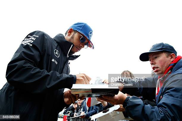 Lewis Hamilton of Great Britain and Mercedes GP signs autographs for fans before practice for the Formula One Grand Prix of Great Britain at...