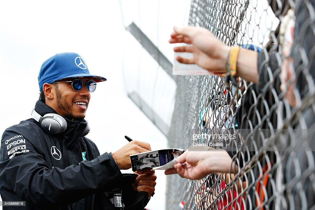 Lewis Hamilton of Great Britain and Mercedes GP signs autographs for fans on the drivers parade before the Formula One Grand Prix of Great Britain at Silverstone on July 10, 2016 in Northampton, England.