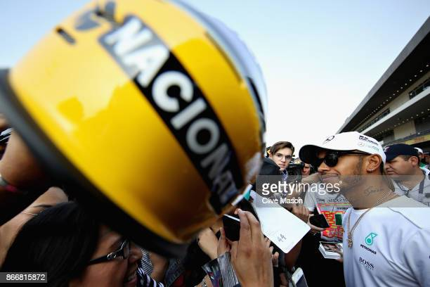 Lewis Hamilton of Great Britain and Mercedes GP signs autographs for fans in the Pitlane during previews to the Formula One Grand Prix of Mexico at...