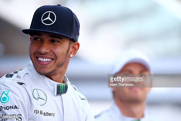 Lewis Hamilton of Great Britain and Mercedes GP smiles as he attends a team photograph with Nico Rosberg of Germany and Mercedes GP before the Abu...