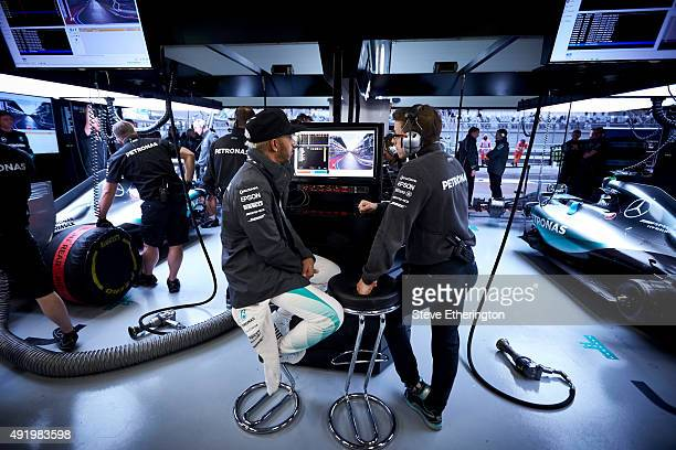 Lewis Hamilton of Great Britain and Mercedes GP speaks with a member of his team in the garage during practice for the Formula One Grand Prix of...