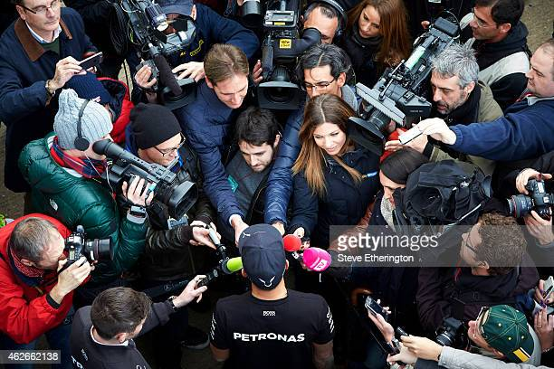 Lewis Hamilton of Great Britain and Mercedes GP speaks with members of the media in the paddock during day two of Formula One Winter Testing at...