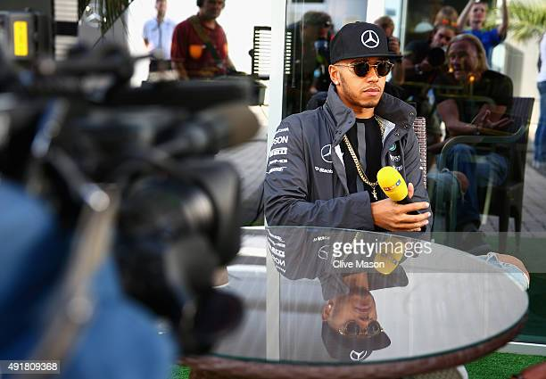Lewis Hamilton of Great Britain and Mercedes GP speaks with members of the media in the paddock during previews to the Formula One Grand Prix of...