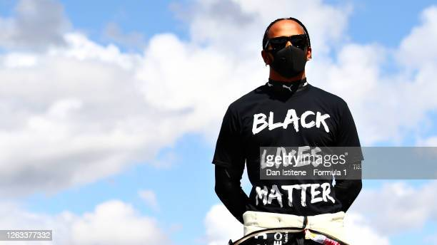 Lewis Hamilton of Great Britain and Mercedes GP stands on the grid wearing a Black Lives Matter shirt before the F1 Grand Prix of Great Britain at...
