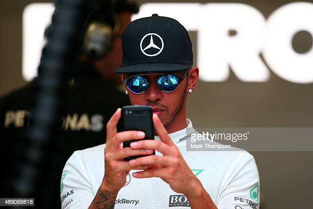 Lewis Hamilton of Great Britain and Mercedes GP takes a photo of his car in the garage with his mobile phone during final practice for the Formula...