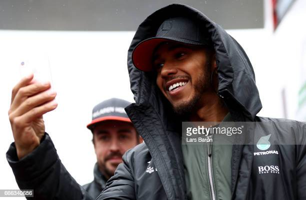 Lewis Hamilton of Great Britain and Mercedes GP takes a photo on his phone on the drivers parade before the Formula One Grand Prix of China at...