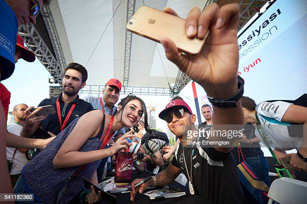 Lewis Hamilton of Great Britain and Mercedes GP takes a photo with a fan during previews ahead of the European Formula One Grand Prix at Baku City...