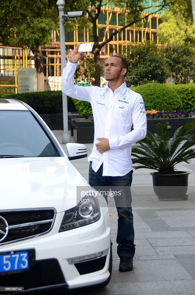 Lewis Hamilton of Great Britain and Mercedes GP takes photos with his smartphone during the filming of a Mercedes-Benz advertisment in front of Jin Mao Tower on April 10, 2013 in Shanghai, China.