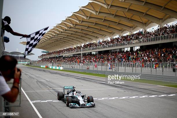 Lewis Hamilton of Great Britain and Mercedes GP takes the chequered flag as he is victorious during the Malaysia Formula One Grand Prix at the Sepang...