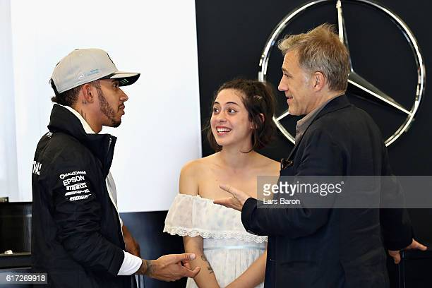 Lewis Hamilton of Great Britain and Mercedes GP talks with actors Christoph Waltz and Rosa Salazar in the garage during final practice for the United...