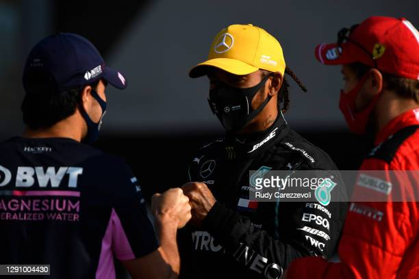 Lewis Hamilton of Great Britain and Mercedes GP talks with Sergio Perez of Mexico and Racing Point and Sebastian Vettel of Germany and Ferrari on the...