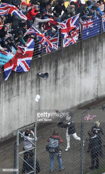 Lewis Hamilton of Great Britain and Mercedes GP throws caps to the fans during practice for the Formula One Grand Prix of China at Shanghai...