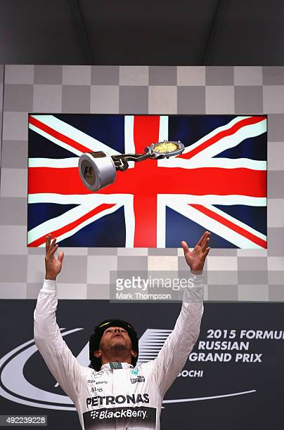 Lewis Hamilton of Great Britain and Mercedes GP throws the trophy in the air as he celebrates on the podium after winning the Formula One Grand Prix...