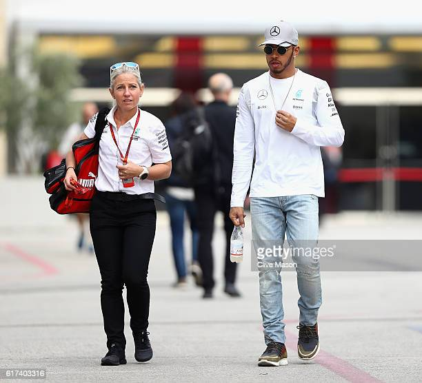 Lewis Hamilton of Great Britain and Mercedes GP walks in the Paddock with trainer Angela Cullen before the United States Formula One Grand Prix at...