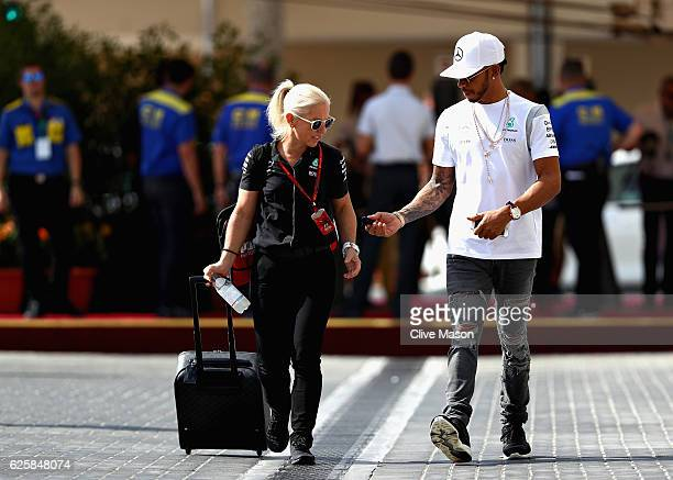 Lewis Hamilton of Great Britain and Mercedes GP walks in the Paddock with trainer Angela Cullen before final practice for the Abu Dhabi Formula One...