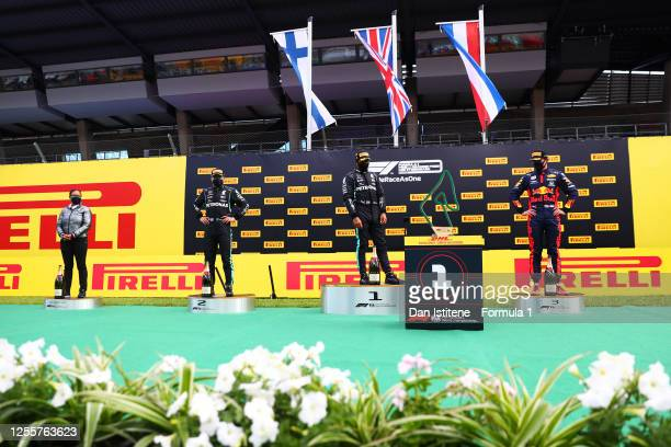 Lewis Hamilton of Great Britain and Mercedes GP watches next to Max Verstappen of Netherlands and Red Bull Racing and Valtteri Bottas of Finland and...
