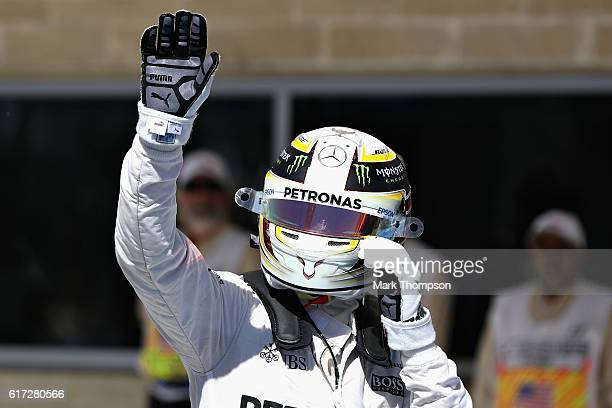 Lewis Hamilton of Great Britain and Mercedes GP waves to the crowd after qualifying in pole position during qualifying for the United States Formula...
