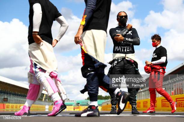 Lewis Hamilton of Great Britain and Mercedes GP wears a tshirt displaying the message 'Black Lives Matter' as he stands at the front of the grid in...
