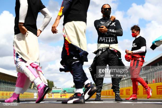 Lewis Hamilton of Great Britain and Mercedes GP wears a t-shirt displaying the message 'Black Lives Matter' as he stands at the front of the grid in...