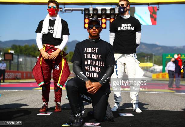 Lewis Hamilton of Great Britain and Mercedes GP wears a tshirt displaying the message 'arrest the cops who killed Breonna Taylor' as he takes a knee...