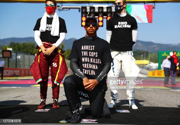 Lewis Hamilton of Great Britain and Mercedes GP wears a t-shirt displaying the message 'arrest the cops who killed Breonna Taylor' as he takes a knee...