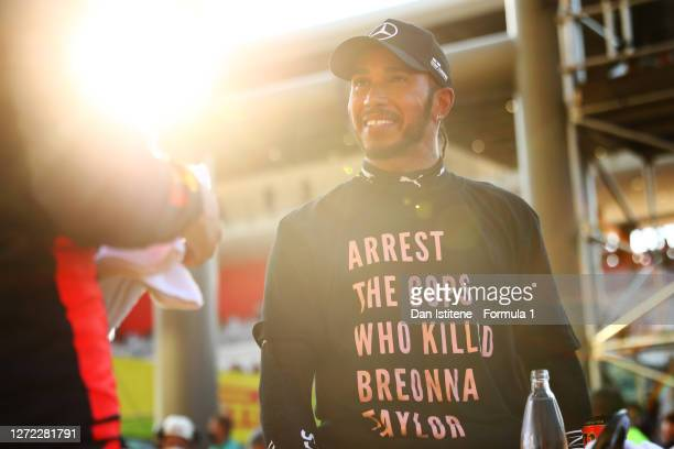 Lewis Hamilton of Great Britain and Mercedes GP wears a t-shirt displaying the message 'arrest the cops who killed Breonna Taylor' as he celebrates...