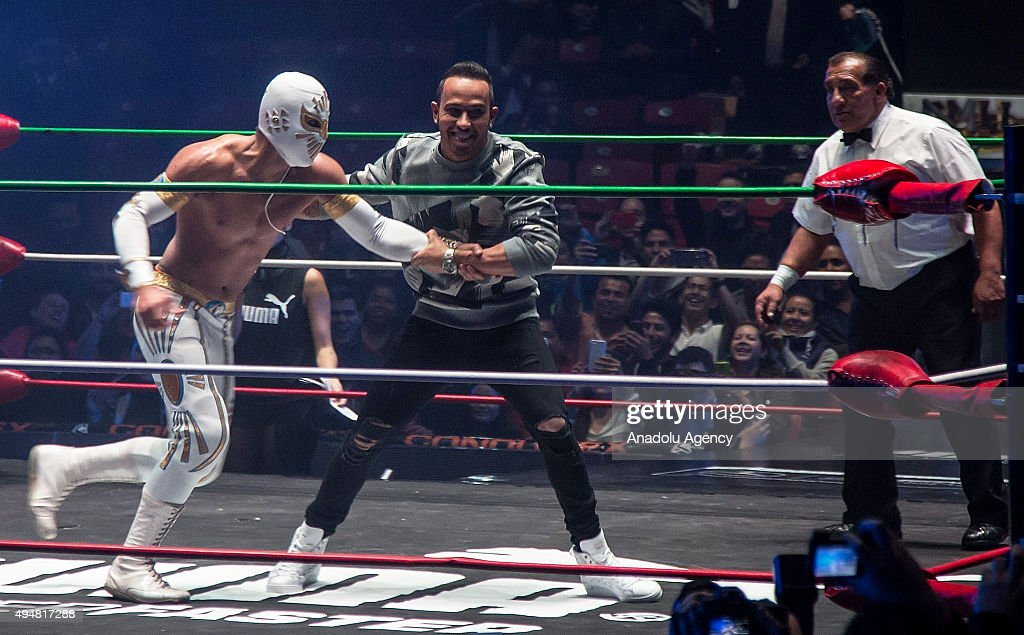 Lewis Hamilton of Great Britain and team Mercedes (R) pretends to fight with Mexican 'Lucha Libre' wrestler Mistico (L) during a promotional event in Mexico City, Wednesday, Oct. 28, 2015. Mexico will hold its first Formula One race in 23 years on Sunday at the Hermanos Rodriguez race track.