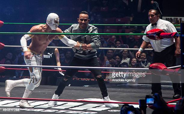 """Lewis Hamilton of Great Britain and team Mercedes pretends to fight with Mexican """"Lucha Libre"""" wrestler Mistico during a promotional event in Mexico..."""