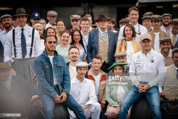 Lewis Hamilton of Great Britain and Valtteri Bottas of Finland surrounded by Mercedes AMG Petronas F1 Team members pose for a photo prior to the...